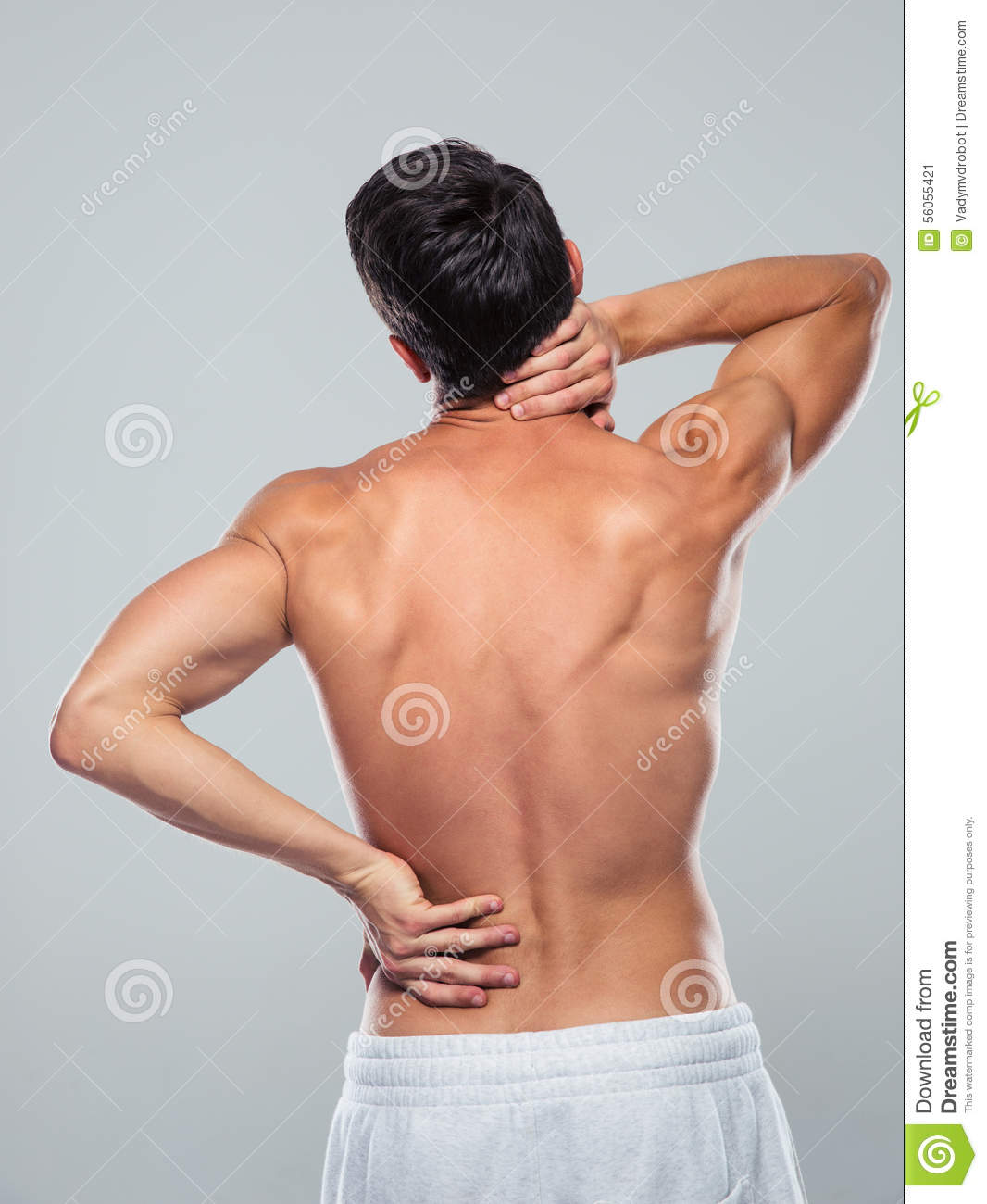 Back view portrait of a fitness man standing with back pain over gray ...