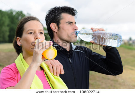 Sport couple drinking water and isotonic drink after training together ...