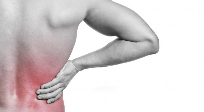 Muscular young man holding his back in pain, isolated on white b