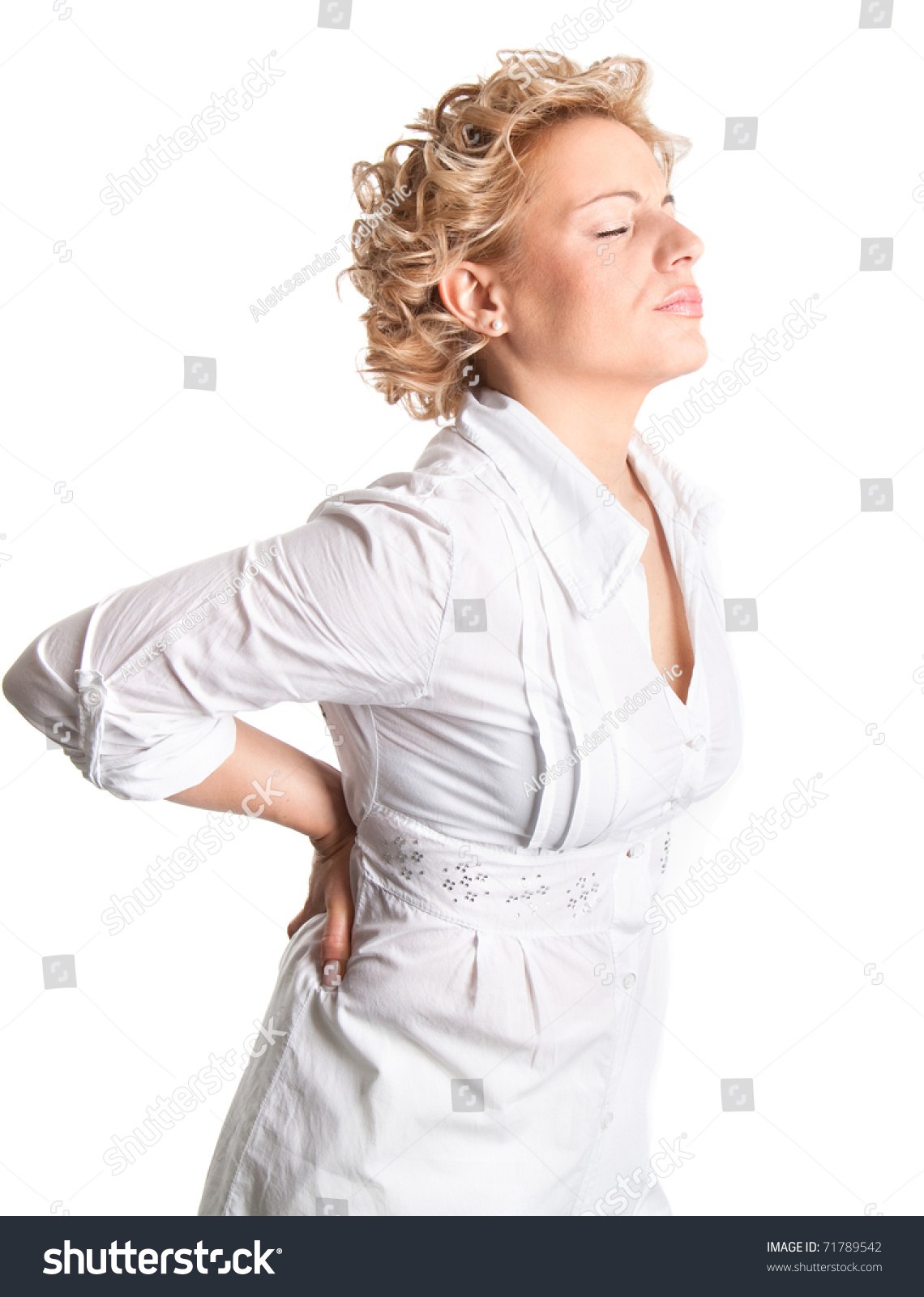 Hurting Back Pain. Young Woman Holds Her Back In Pain. Stock Photo ...