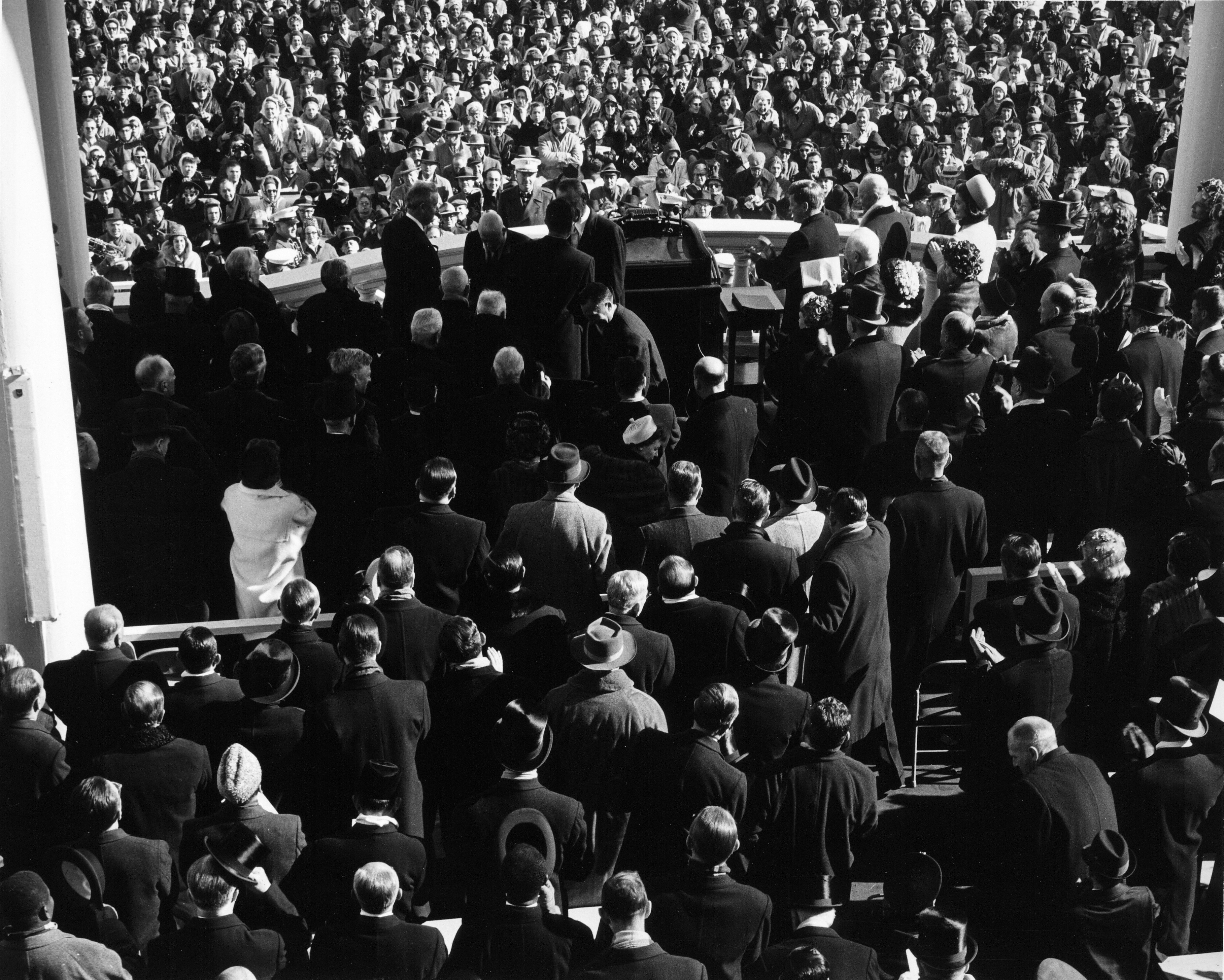 The Inauguration of John F. Kennedy as seen from behind. The few top hats in the crowd can be distinguished by the shininess of the hat\u0027s flat crown