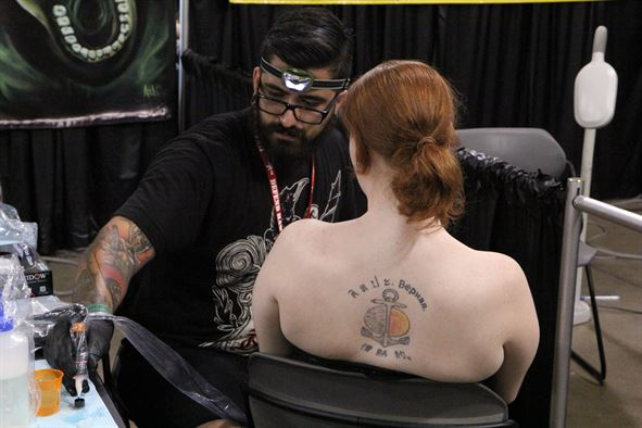 A member of the U.S. Navy sits for a tattoo with one of the many renowned