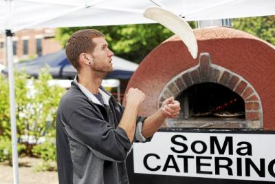 Travis Deinlein, manager of SoMa Catering, flips dough for personal ...