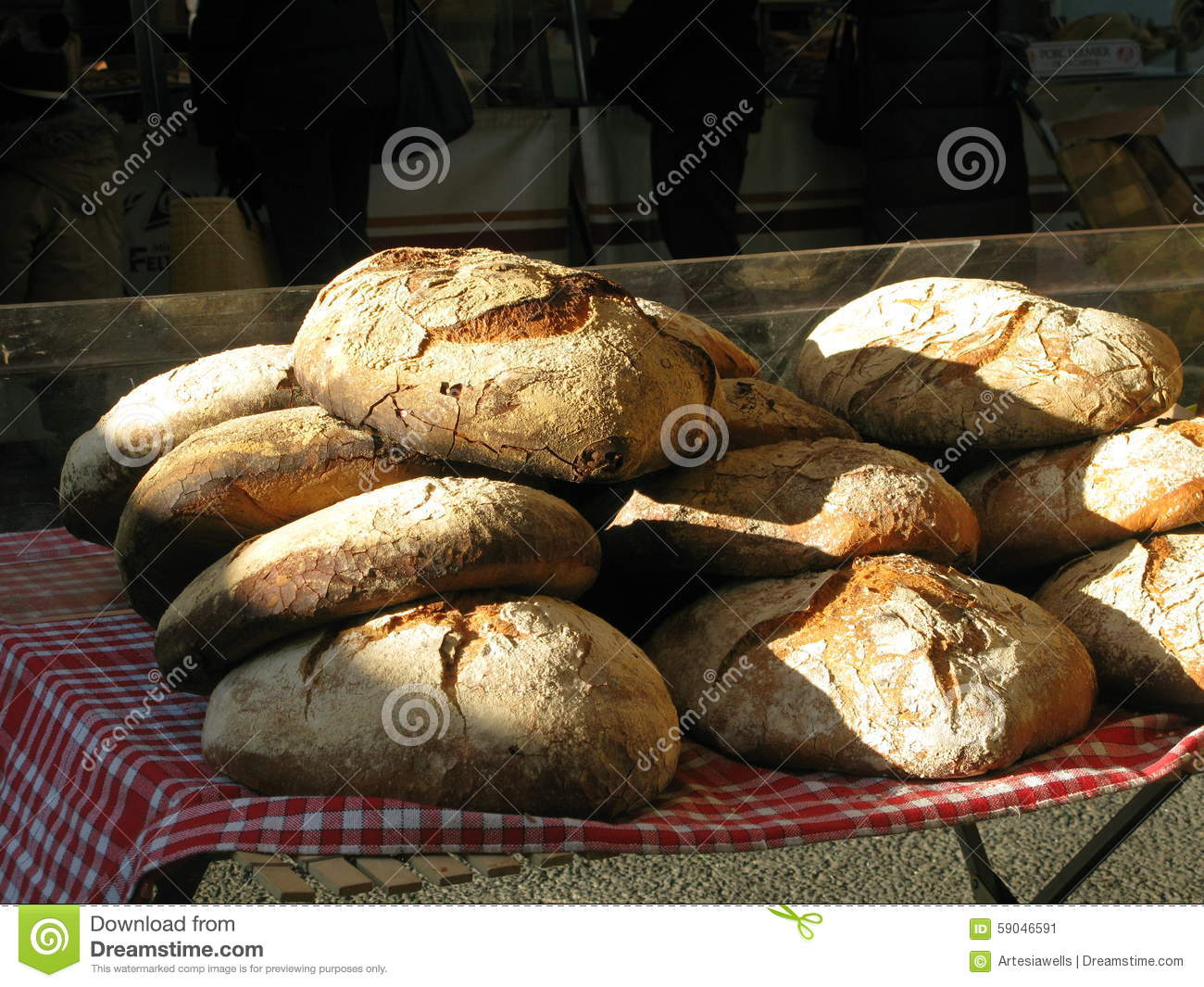 Market bread on red and white checkered cloth in bright morning light ...