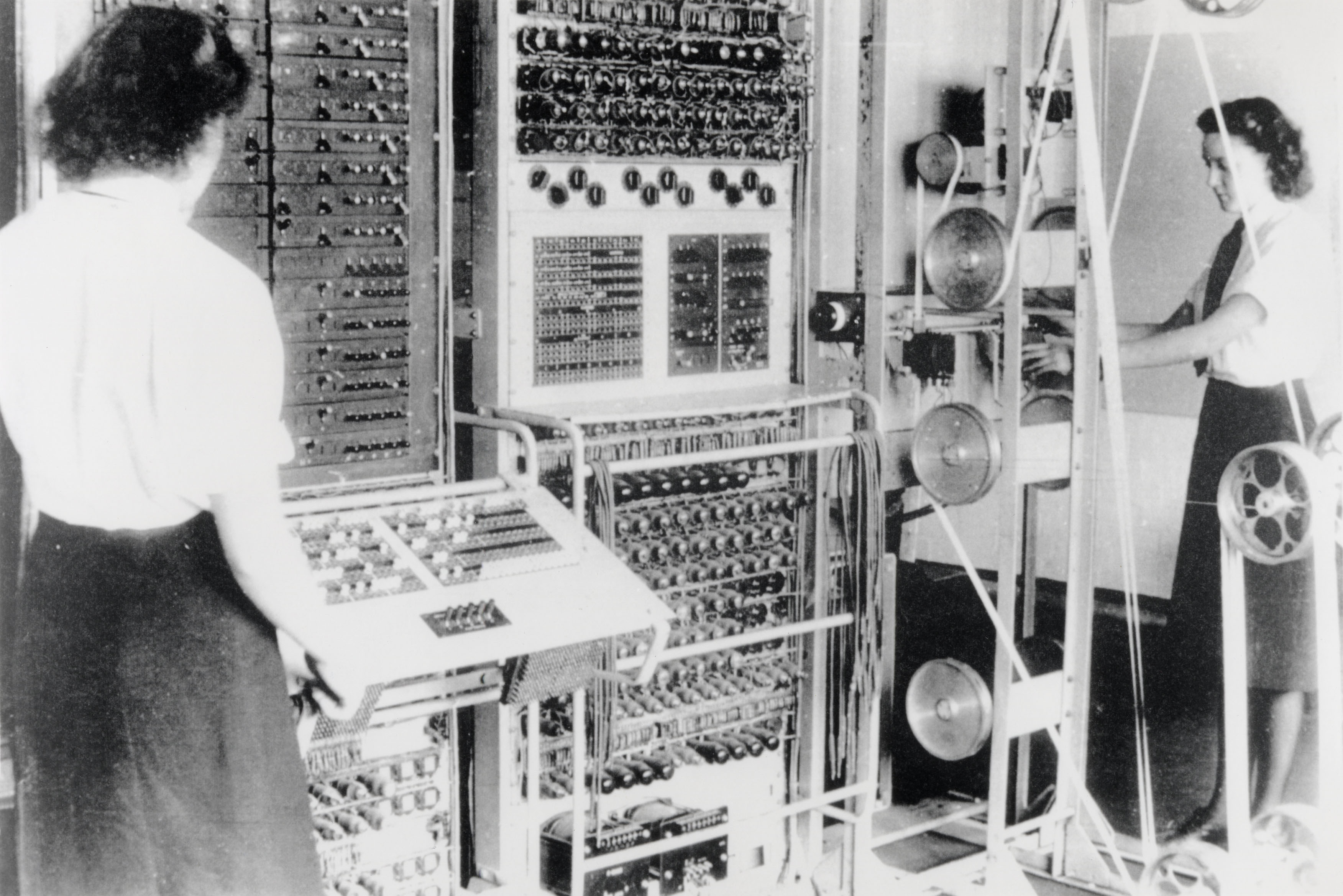 A Mark 2 Colossus computer. The Wren operators are (left to right) Dorothy Du Boisson and Elsie Booker. The slanted control panel on the left was used to ...